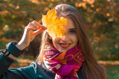 Portrait of a beautiful young girl who keeps  sheet near the eyes and smiles close up Stock Photos