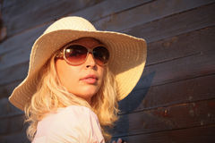Portrait of beautiful young girl wiht sunglases and hat, wood door background Royalty Free Stock Photos