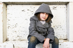 Portrait of a beautiful young girl in winter coat and jeans. A portrait of a beautiful young girl in a winter coat and jeans with dirty knees sitting against a Stock Image
