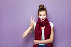 Portrait of beautiful young happy smiling woman, showing two fingers or victory gesture, dressed white t-shirt and red scarf on pu. Rple background Royalty Free Stock Image