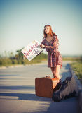 Portrait of beautiful young hippie woman hitchhiking on a road Stock Photos