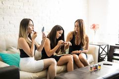Sexy woman and friends going out. Portrait of a beautiful young Hispanic women putting on some lipstick while she and her friends get ready for a night out Royalty Free Stock Image