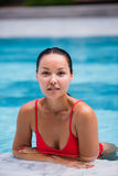 Portrait of beautiful, young lady in red bikini sitting poolside in luxury hotel Royalty Free Stock Image
