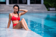 Portrait of beautiful, young lady in red bikini sitting poolside in luxury hotel Stock Image