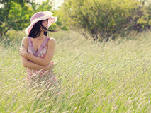 Portrait of beautiful young lady standing on summer meadow. Portrait of the beautiful young lady walking in nature on sunny summer day royalty free stock photography