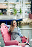 Portrait of beautiful young lady in sunglasses sitting in elegant armchair. Pretty girl in grey dress smiling on blurred embankment cafe outdoor background Stock Image