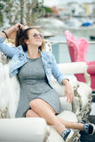 Portrait of beautiful young lady in sunglasses sitting in elegant armchair. Royalty Free Stock Photos
