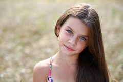 Portrait of a beautiful young little girl. Portrait of a beautiful blonde little girl on the background of wheat field Royalty Free Stock Photography