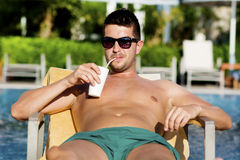 Portrait of beautiful young man drinking juice on the pool Stock Photos
