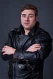 Young man in a leather jacket on a gray background Royalty Free Stock Photography