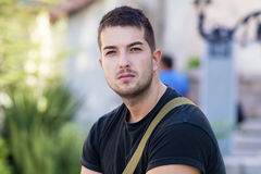 Portrait of beautiful young man sitting on the street Stock Images