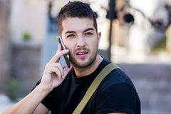 Portrait of beautiful young man talking on the phone outdoor. Portrait of beautiful man talking on the phone outdoor stock photo