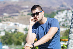 Portrait of beautiful young man talking on the phone outdoor Royalty Free Stock Images