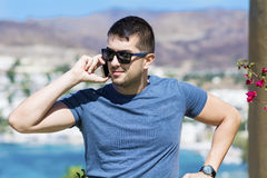 Portrait of beautiful young man talking on the phone outdoor Stock Image