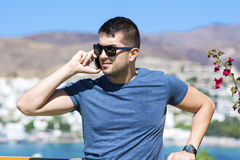 Portrait of beautiful young man talking on the phone outdoor Royalty Free Stock Photography