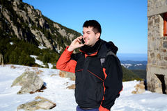 Portrait of beautiful young man talking on the phone in the winter mountain Royalty Free Stock Photos