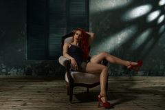 Woman in fashionable chair. Portrait of beautiful young model sitting in fashionable chair stock image