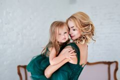 Portrait of a beautiful young mother with a cute blonde daughter sitting in white interior dressed in elegant green. Dresses Stock Photo