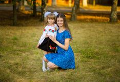 Portrait of beautiful young mother hugging first-grader daughter in festive school uniform on background autumn park. Parent take child to primary school stock photo