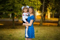 Portrait of beautiful young mother hugging first-grader daughter in festive school uniform on background autumn park. Parent take child to primary school royalty free stock image