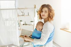Portrait of a beautiful young mother with sleeping son on chest and book in hands. Woman turns head around to look on stock photography