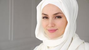 Portrait of muslim arabian woman wearing hijab, looking at camera and smiling. Portrait of beautiful young muslim arabian woman wearing white hijab, slowly stock footage