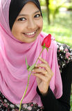 Portrait of beautiful young muslim girl. Holding a red rose flower at park Stock Photo