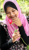 Portrait of beautiful young muslim girl. Holding a red rose flower at park Stock Photography