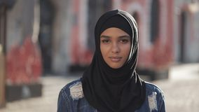 Portrait of beautiful young Muslim woman wearing hijab headscarf looking into the camera standing on the old city stock video