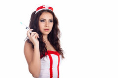 Portrait of a beautiful young nurse with syringe. Portrait of a sexy young nurse with long curly hair holding a syringe on isolated white background. High Stock Image