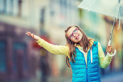 Portrait of beautiful young pre-teen girl with umbrella under rain Stock Photo