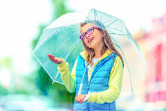 Portrait of beautiful young pre-teen girl with umbrella under rain Stock Photos