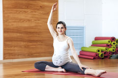 Portrait of a beautiful young pregnant woman doing exercises. Working out, yoga and fitness, pregnancy concept. Stock Image