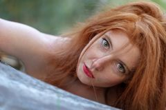Portrait of a beautiful young red-haired woman with green eyes is sensually leaning against a fallen gray tree trunk. Portrait of a beautiful young red-haired stock photo