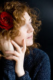 Portrait of beautiful young redhead with curly red rose Royalty Free Stock Photos