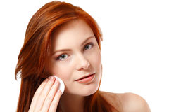 Portrait of beautiful young redheaded woman delete cosmetics wit Stock Photo