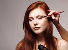 Portrait of beautiful young redheaded woman with esthetician mak Stock Photos