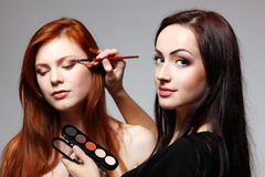 Portrait of beautiful young redheaded woman with esthetician making makeup. Portrait of beautiful young redheaded women with esthetician making makeup eye shadow stock photography