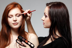 Portrait of beautiful young redheaded woman with esthetician making makeup eye shadow. Portrait of beautiful young redheaded women with esthetician making makeup royalty free stock photos