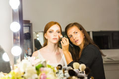 Portrait of beautiful young redheaded woman with esthetician making makeup eye shadow Royalty Free Stock Photo