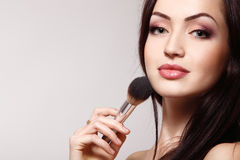 Portrait of beautiful young redheaded woman with makeup brush Stock Image