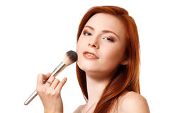 Portrait of beautiful young redheaded woman with makeup brush. Stock Photo