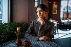 Portrait of beautiful young retro lady in cafe. Sitting near window. Beautiful young lady resting in a cafe and looking at camera. Serious brunette waiting for Stock Image