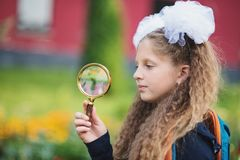 Portrait of a beautiful young Schoolgirl looking through a magnifying glass and sitting at a desk. On the background autumn park. Farewell Bell. day of royalty free stock photo