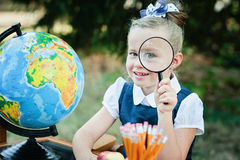 Portrait of a beautiful young Schoolgirl looking through a magnifying glass and sitting at a desk Royalty Free Stock Image