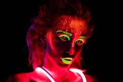 Portrait of a beautiful young girl in neon lent with ultraviolet paint on her body. Pretty woman with glowing royalty free stock photos