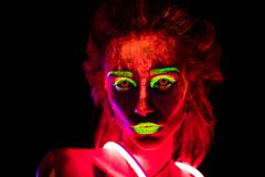 Portrait of a beautiful young girl in neon lent with ultraviolet paint on her body. Pretty woman with glowing royalty free stock image