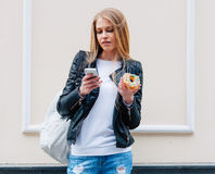 Portrait of a beautiful young sexy woman eating a donut, looks at her smart phone on the street European city. Outdoor. Stock Photos