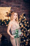 Portrait of beautiful young smiling blonde woman wearing Golden dress and holding gift box on Christmas background royalty free stock image