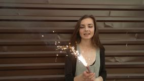 Portrait of beautiful young smiling girl on the background of the metal wall, holding sparkler in her hands and looking. Very happy, slow motion shot, retro stock footage